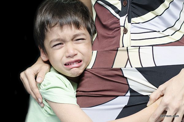 Littleboy crying holding his mother black background