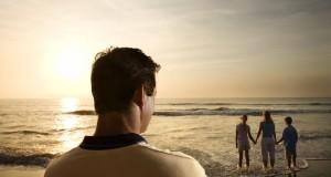 Man watching family at beach