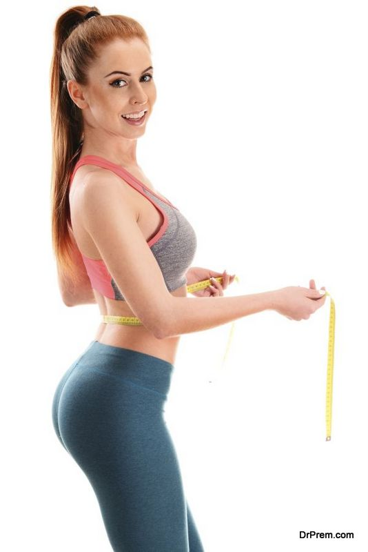 Young woman measuring herself. Weight loss bad habits
